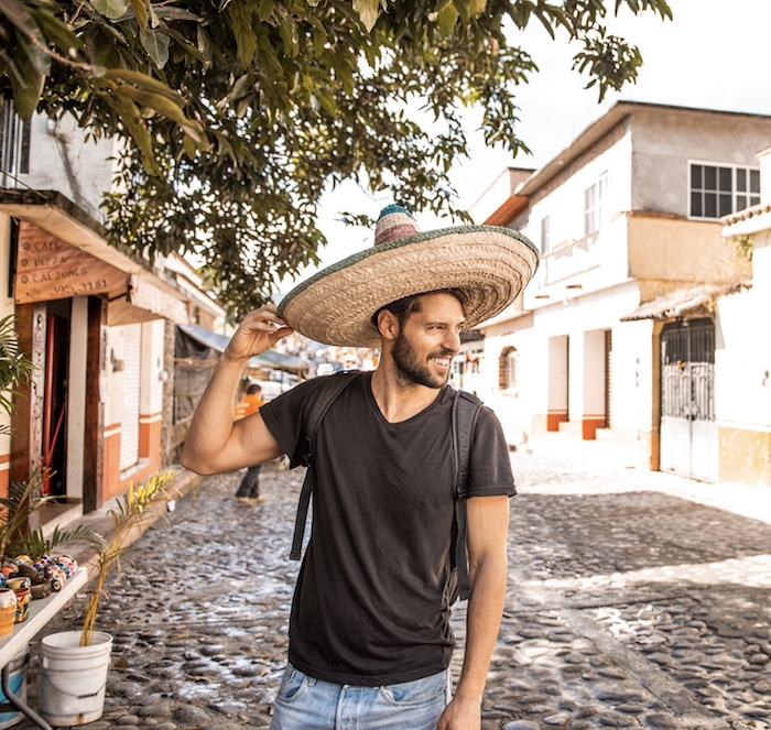 Smiling caucasian tourist wearing sombrero in streets of Cancun