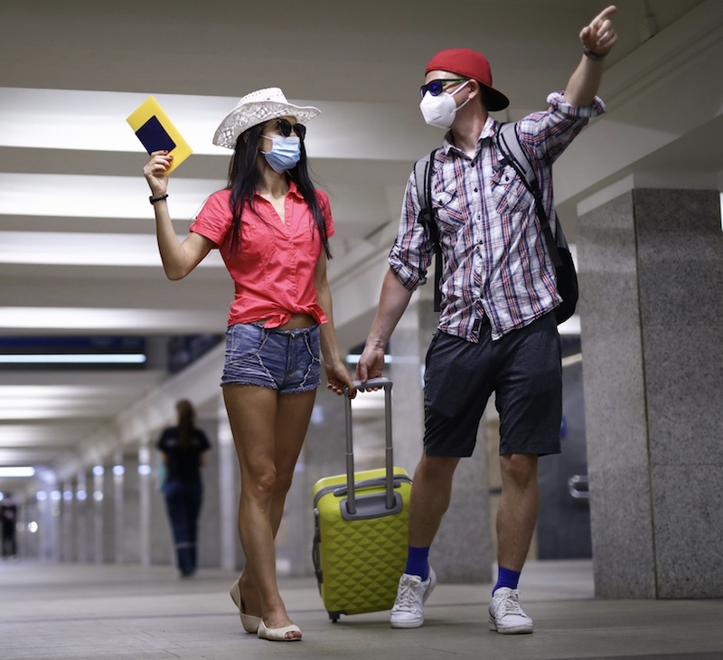 couple masks heading for vacation airport