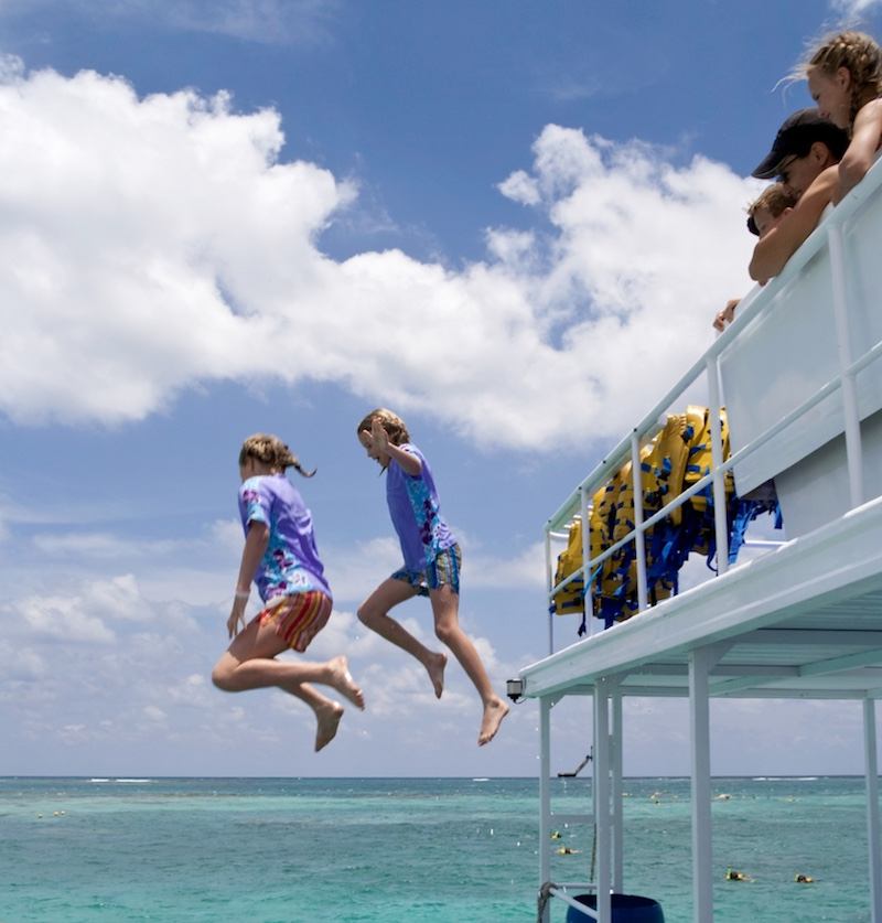 tourists jumping in cancun waters